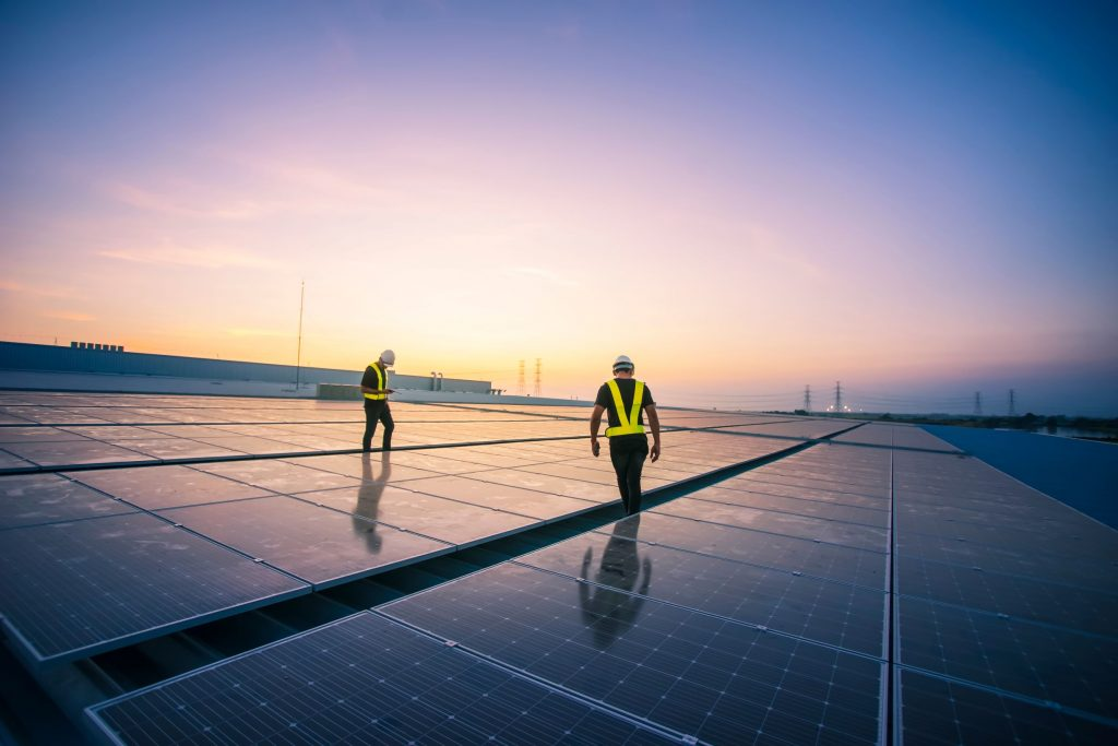engineers checking solar panel installation on factory roof