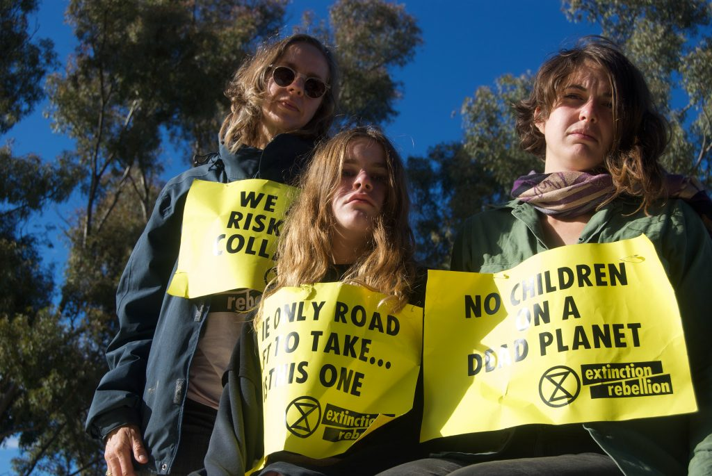 committed climate activists Anthea, Mary and Violet with Extinction rebellion protest