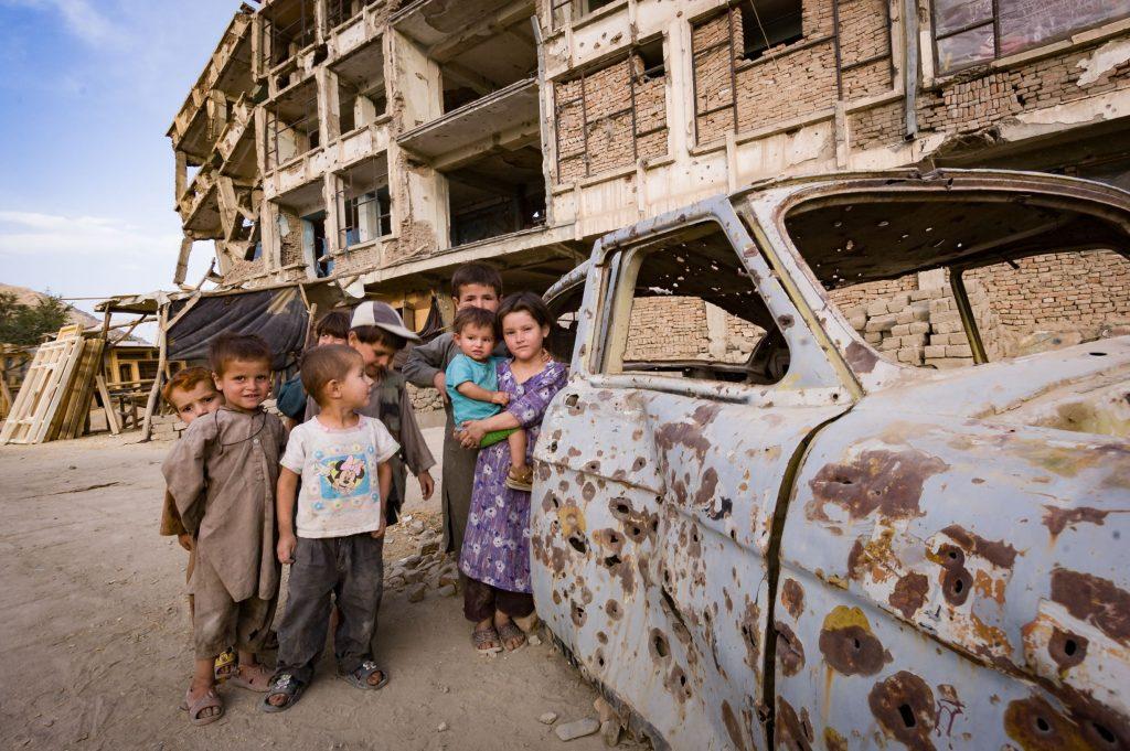 children play around bullet-ridden car in Kabul, Afghanistan