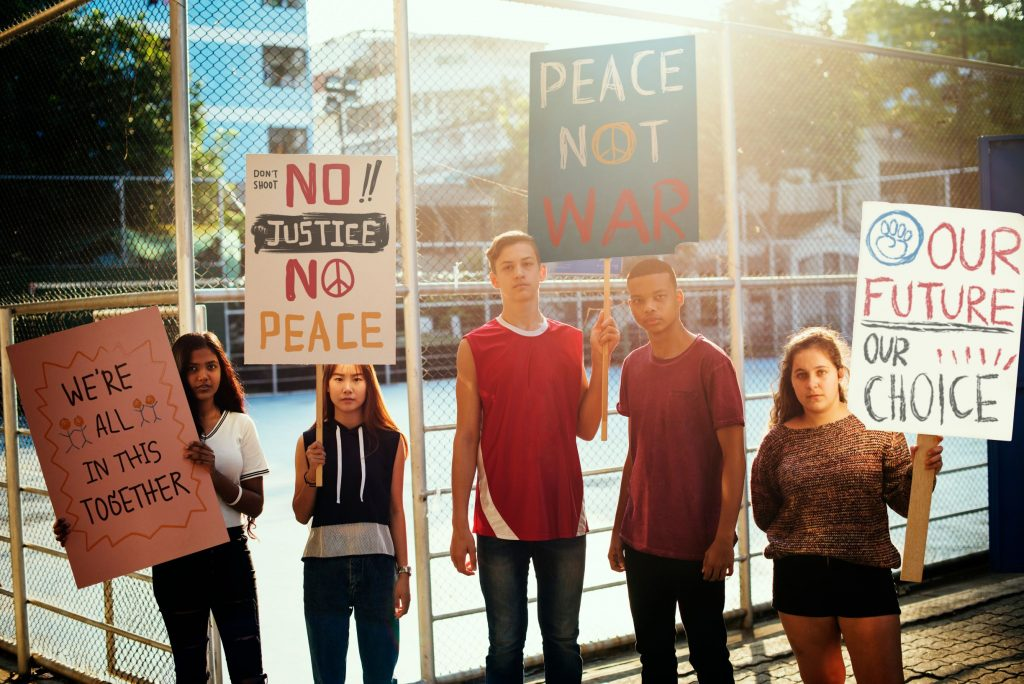 A group of young people holding protest signs asking for justice and peace and saying no to war