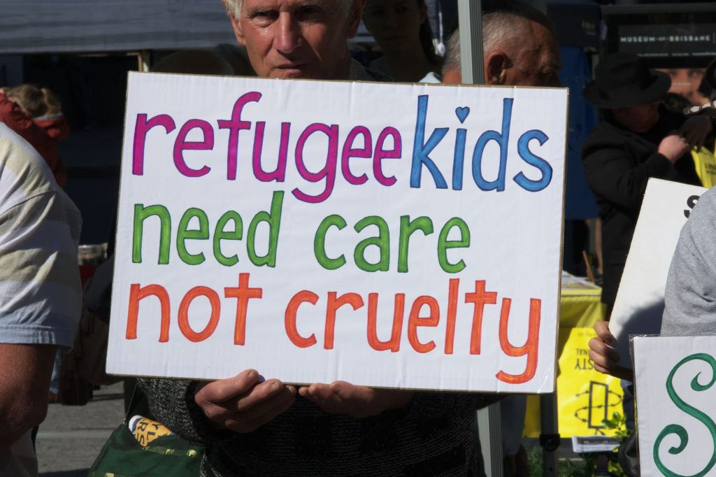 a proetst sign at World Refugee Day in June 2020 saying Refugee Kids Need Care Not Cruelty