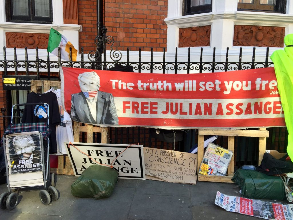 protest signs in front of the Ecuadorian Embassy in London to free Julian Assange