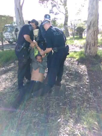 Police arresting peaceful protester at Huskisson Church site dragging him along the ground by his arms