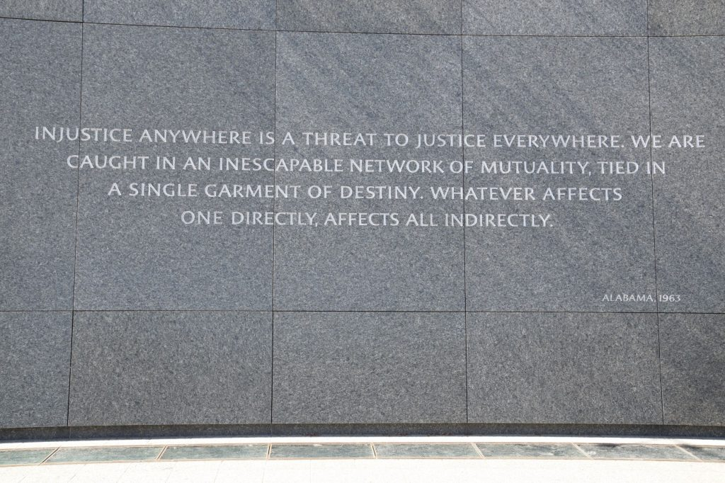 Sign at Martin Luther King Jr. Memorial in Washington DC Injustice Anywhere is a Threat to Justice Everywhere. We are Caught in an Inescapable Network of Mutuality, Tied in a Single Garment of Destiny. Whatever Affects One Directly, Affects all Indirectly