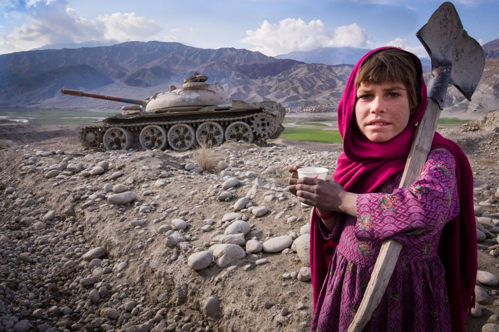 Children are used to abandoned tanks in the landscape of Afghanistan