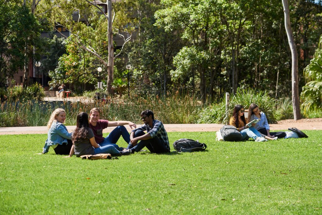 Students socialising on grass outside University of Wollongong during lecture break